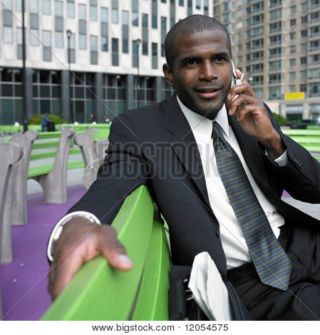 Businessman sitting on bench talking on cell phone