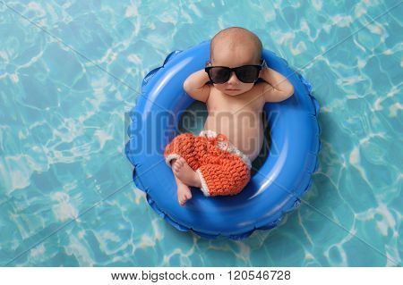 Newborn Baby Boy Floating On An Inflatable Swim Ring