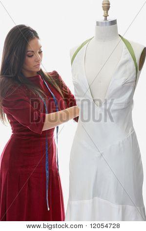 Dressmaker sewing on mannequin