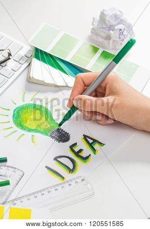 Designer Drawing A Light Bulb. Brainstorming Cocnept.