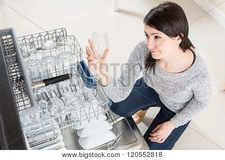 Woman Using A Dishwasher In A Modern Kitchen.