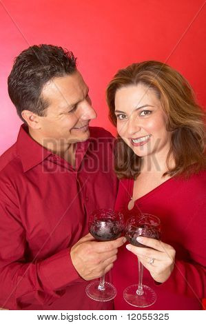 Hispanic couple drinking red wine