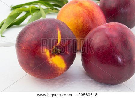 Ripe Red And Orange Nectarines On White Wood Background
