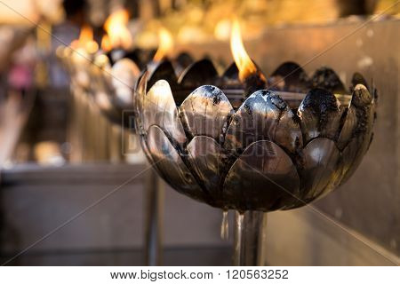 The Buddhist's tradition to make merit by filling oil in the lamp at many many temples in Thailand. They believe to bring healthiness and longevity.