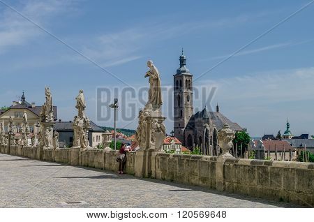 Kutna Hora , Czech Republic - May 7,2012: Statues in front of Jesuit College in Kutna Hora  with St. James Church (Kostel svateho Jakuba) in background.
