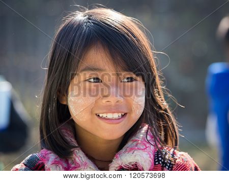 INLE LAKE MYANMAR - JANUARY 13 2016: Unidentified young Myanmar girl with thanaka on her smile face is happiness. Thanaka is a yellowish-white cosmetic paste made from ground bark.