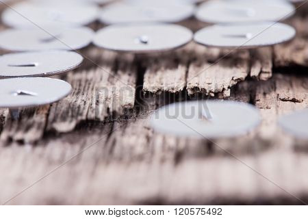 abstract rotten wooden board and round metal pushpin, selective focus
