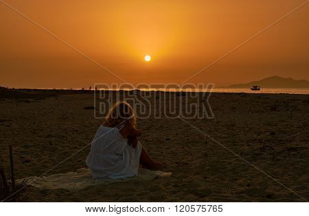 A girl in a white dress on a sandy beach during sunset