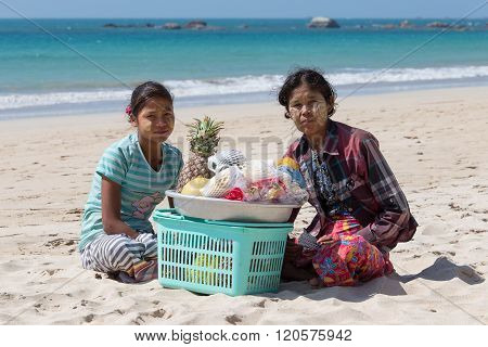 NGAPALI MYANMAR - JANUARY 24 2016: Unidentified women selling fresh fruits at the shoreline to tourists in Ngapali beach. Selling products to the tourists is the main income for people in Ngapali.