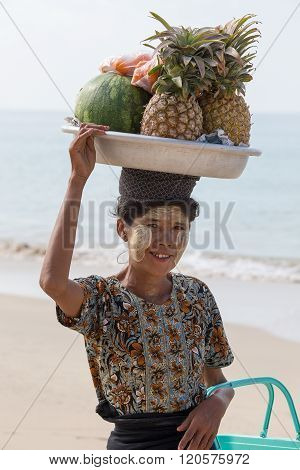 NGAPALI MYANMAR - JANUARY 25 2016: Unidentified woman selling fresh fruits at the shoreline to tourists in Ngapali beach. Selling products to the tourists is the main income for people in Ngapali.