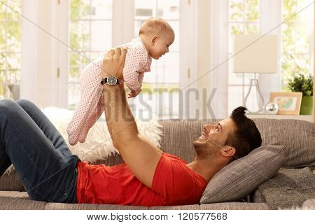 Happy young father lying on sofa, lifting baby girl high up, smiling, having fun. Side view.