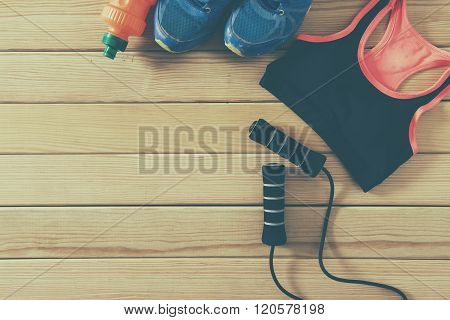 Sport shoes and clothes on wooden background