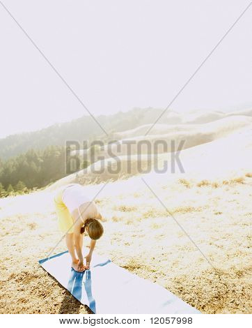 Senior woman stretching on a yoga mat outdoors