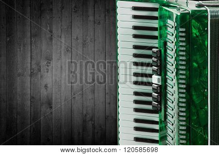 Part green accordion on wooden grey background. Write text
