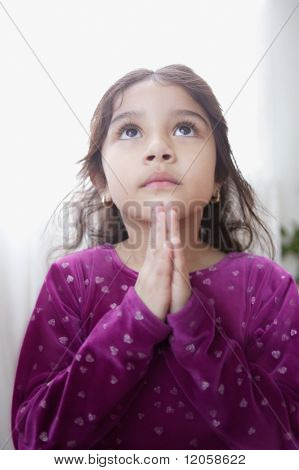 Young girl praying with her hands together