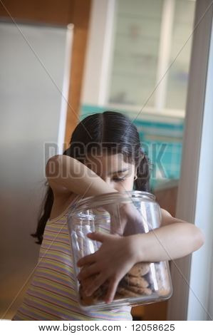 Girl taking cookie from cookie jar