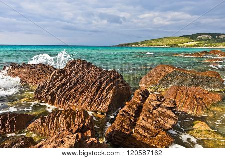 Red rocks and turquoise water at beach in San Pietro island, Sardinia