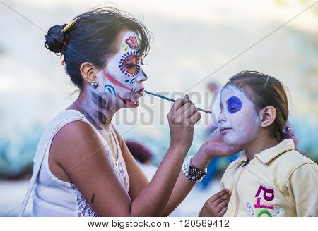OAXACA MEXICO - NOV 02 : Unidentified participant has his face covered with makeup on a carnival of the Day of the Dead in Oaxaca Mexico on November 02 2015.