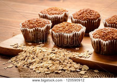 Oat muffins on brown wooden board.