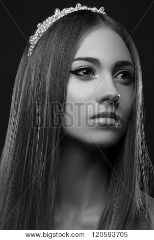 Beautiful girl with a crown on his head a portrait of a beautiful girl studio evening makeup princess queen glamorous young girl dreamy girl black background in studio black and white