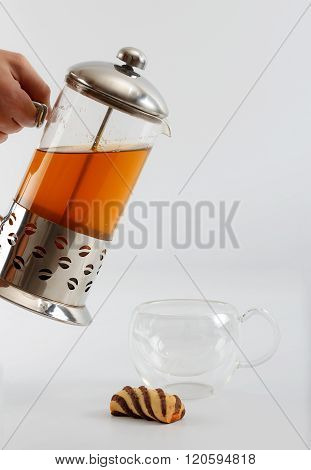 Process Of Pouring Tea From A Teapot Into A Double Sided Glass With A Cookie By Side