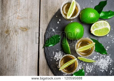 Still life, food and drink, holidays concept. Gold mexican tequila shot with lime and salt on a grunge wooden table. Selective focus, top view, copy space