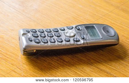 Old cordless phone on a wooden table