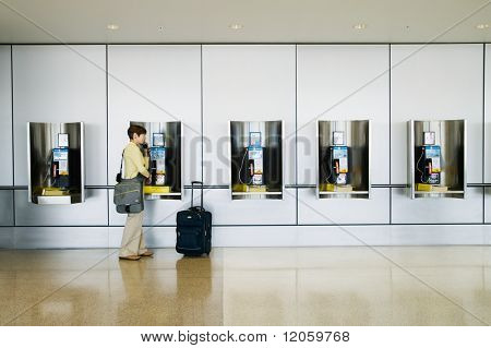 Woman talking on payphone at airport