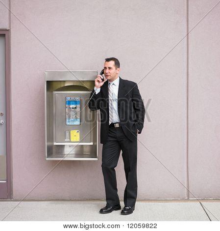 Businessman talking on payphone