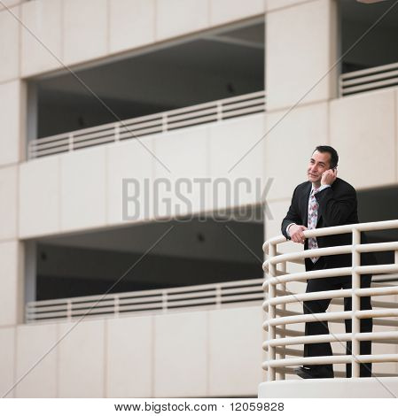 Businessman leaning against railing while talking on cell phone