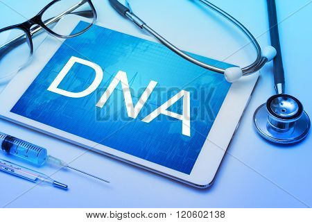 DNA word on tablet screen with medical equipment
