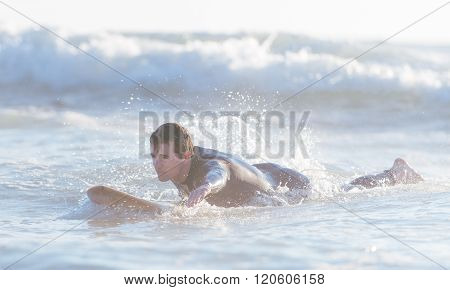 Young Surfer Swimming In The Ocean And Getting Ready To Catch The Next Wave
