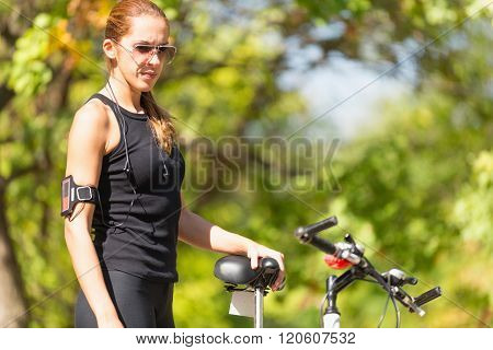Female Biker Standing Next To Bicycle