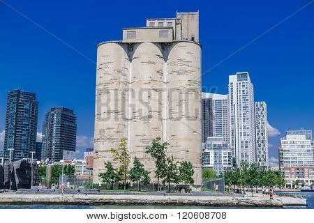 Old vintage Canada Malting plant standing at waterfront between modern buildings