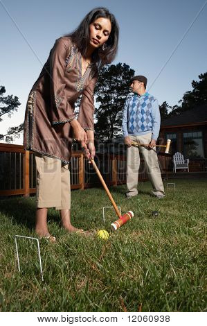 Couple playing croquet in yard