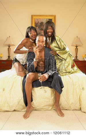 Man in bed with two women