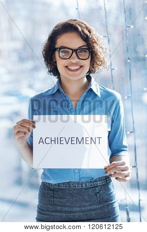 Smiling woman holding sheet of paper