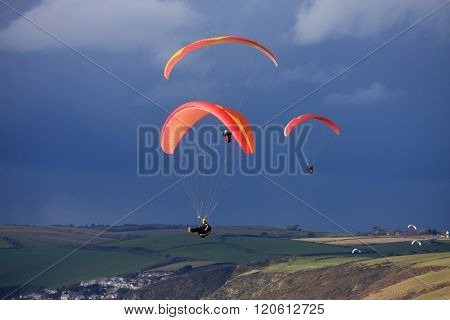 paragliders flying above Whitsand Bay in Cornwall
