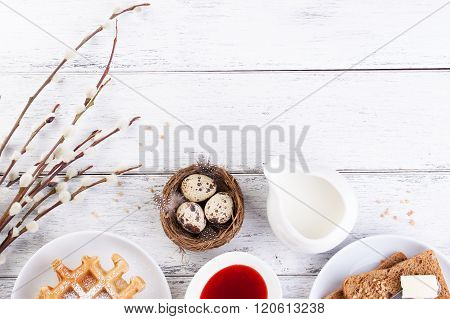 Easter breakfast with quail eggs waffles fruit jam milk and sandwiches with willow branch on a white