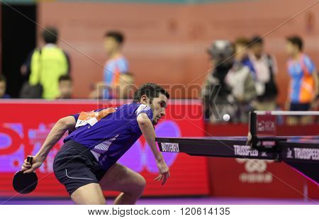 KUALA LUMPUR, MALAYSIA - MARCH 01, 2016: Emmanuel Lebesson of France plays a return shot in his match in the Perfect 2016 World Team Table-tennis Championships held in Kuala Lumpur, Malaysia.