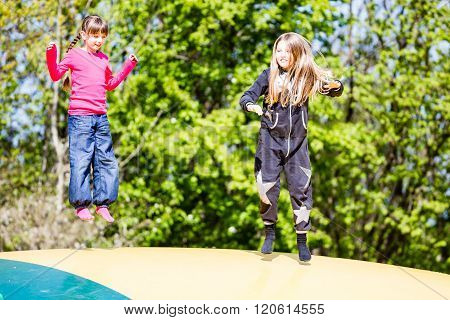 Smiling Young Girls Jumping On Bouncing Pad