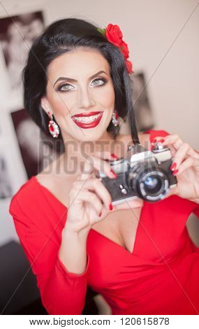 Beautiful young woman with creative make-up and hair style taking photos with a camera