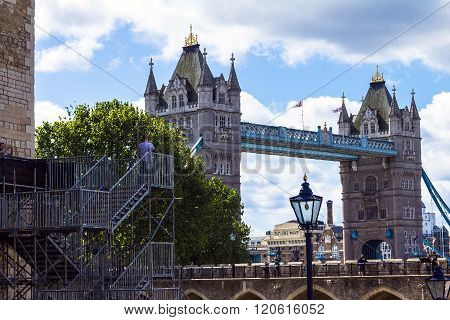 LONDON UK - JUNE 6 2015: Unidentified tourists on Tower Bridge and blue sky background