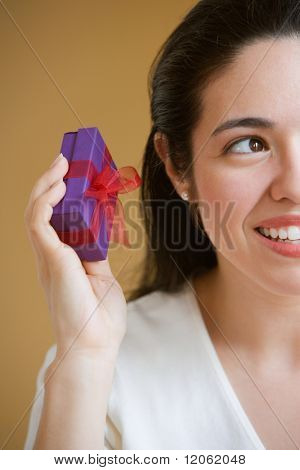 Woman shaking small present to determine what it contains