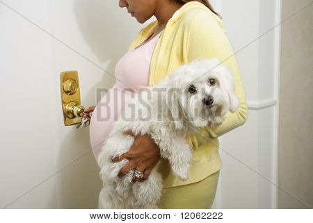 Pregnant woman carrying pet dog