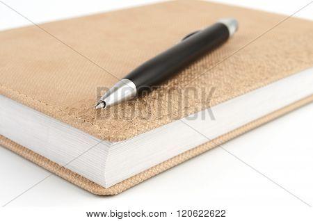 Black Ballpoint Pen On Diary Beige