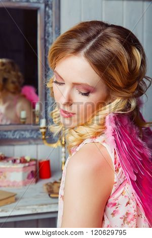 Young beautiful woman in angel costume in the mirror