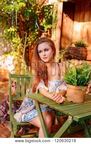 Portrait Of Sexy Young Woman Sitting On A Wooden Chair