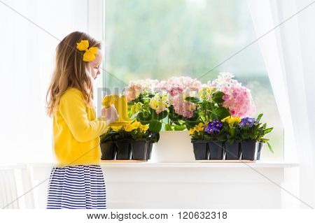 Little Girl Watering Blooming Flowers At Home