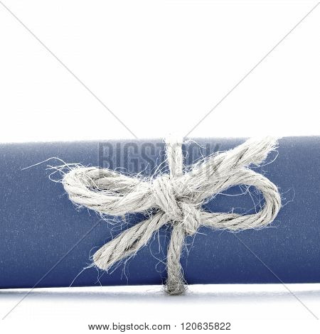 Handmade natural rope knot tied on blue message tube isolated